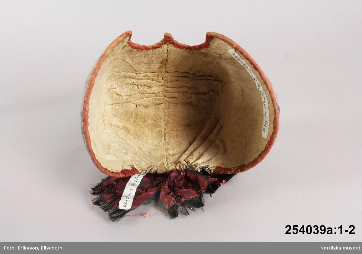 A.Bindmössa av blåviolett sidenatlas med tambursömsbroderi i gulvitt, rosa, ljusbrunt, grönt och svart silke i stiliserat blommönster, vitt foder, nackrosett av mönstervävt sidenband. B. Stycke av tunn bomullslärft kantad med vävd spets skarvad med florsväv, i kanten knypplad spets.  Enligt uppgift från Öster Färnebo sn, men liknar i typ bindmössorna från Ovansjö, som har en speciell form.  Berit Eldvik sept-2005