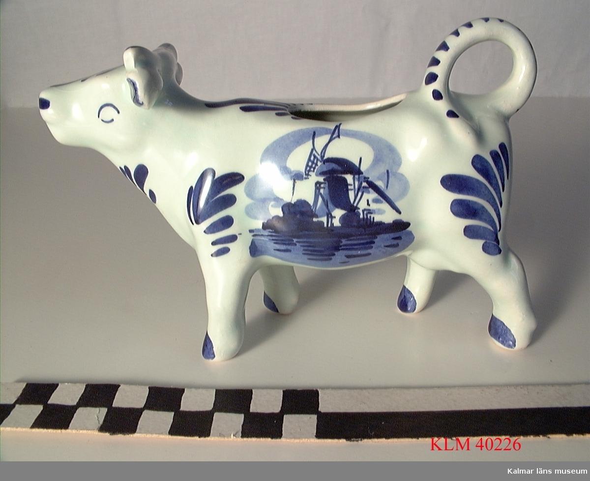 """KLM 40226 Gräddkanna, porslin, i form av en ko. Vit med blå dekor bl a väderkvarn. Stämpel: """"Handpainted Holland""""."""