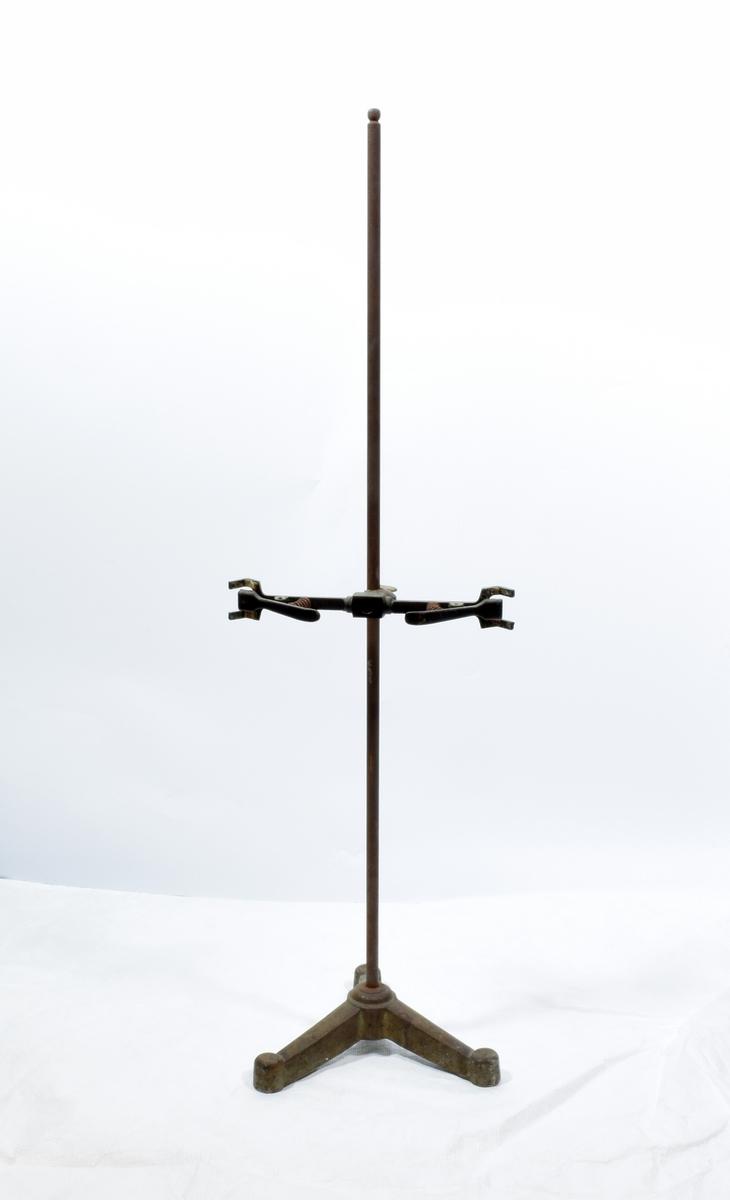 Stativ tll å holde reagensrør, kolber o.l. Stativet består av en lang stang med en jernfot med tre bein. På stangen er det en klype med to armer
