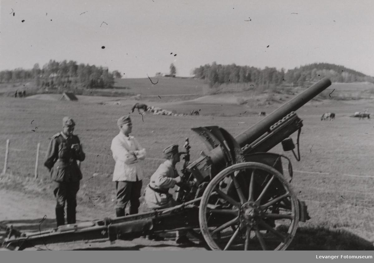 Tre tyske soldater ved artilleri, felthaubitzer 10,5 cm, under øvelse.