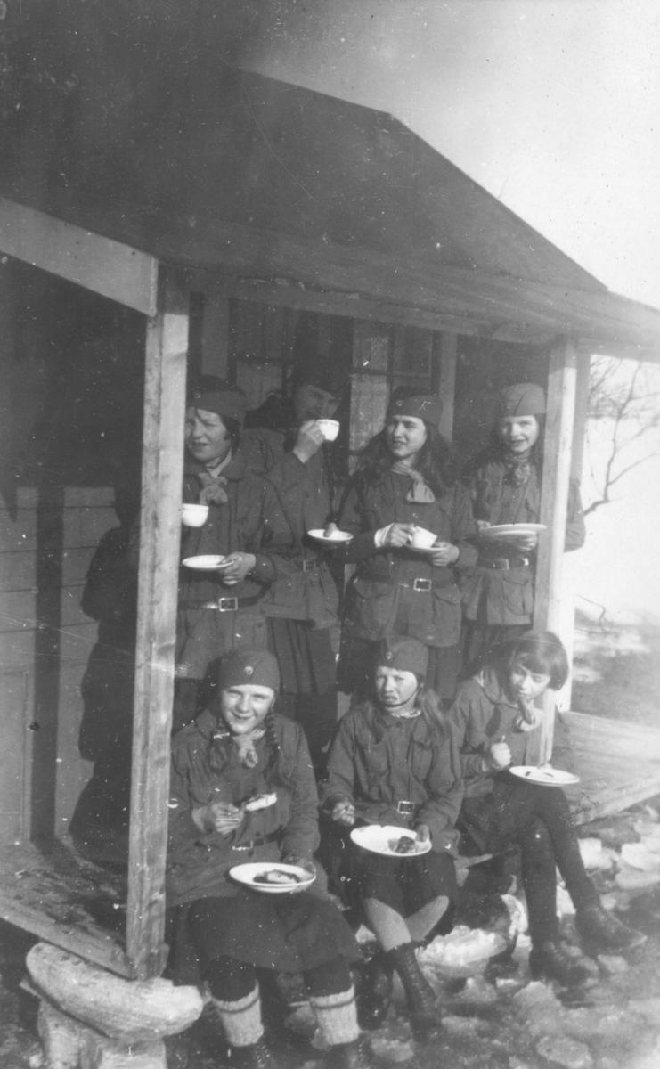 Kløverpatruljen på tur til Hoels hytte i Tomaselv, våren 1930. Jentene er kledt i speideruniformer, og er på trappa foran hytta. De holder kopper og fat i hendene. De er kledt i speideruniformer. Bak fra venstre står: Johanna Dahl, Gjertrud Evanger, Arnhild Tøgersen, og Solveig Evanger. Foran fra venstre sitter: Astrid Pedersen, Randi Feldt, og Aud Johannessen. Det ligger snø på bakken