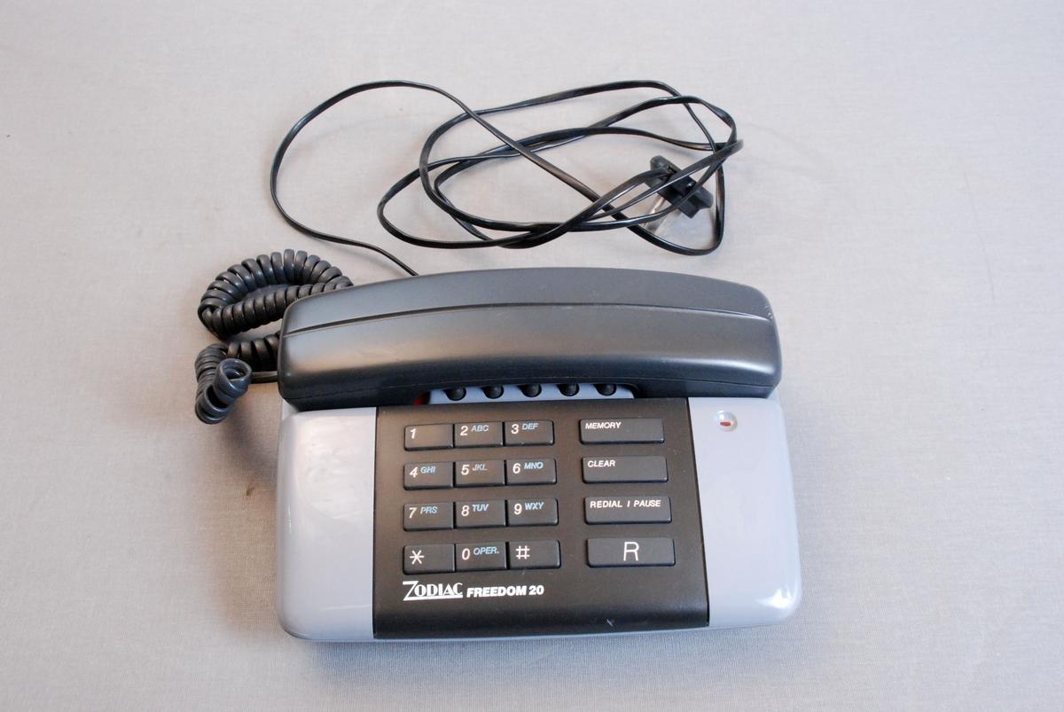 Telefonapparat med tastatur, telefonrør med ledning og kabel for veggkontakt. Apparatet hadde innlagt kode for svar ved varsel om storbrann.