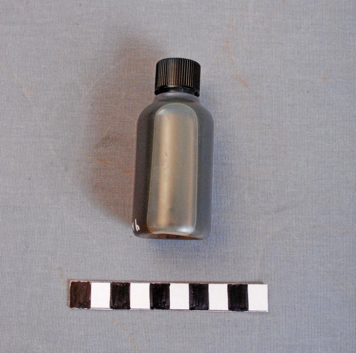 Oljeflaske for bruk til linepistol/redningspistol. Flasken er sylindrisk og har svart plastkork. Inneholder olje.