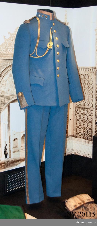 Grupp C I. Ur uniform för officer, Persiska Gendameriet i Persien. Består av vapenrock med överstes gradbeteckning. Vapenrocken är samhörande med långbyxor, ridbyxor, uniformsmössa, ägiljett samt kordong till paradmössa.   Vapenrocken är tillverkad av ljusblå kläde. Enradig med åtta knappar. Axelklaffar av silvertränsar med valknut, samma som till kollett m/1871: Livgardet till häst som knäppes med knappar av mindre format.   Fickor: Två sidofickor och två bröstfickor med treuddiga ficklock. Foder av svart bomullstyg med två innerfickor. Samtliga knappar är av gul metall med persiska statsvapnet. Krage upprättstående, med raka vinkla. På kragen framtill guldgalon 2 cm bred, på kragens båda sidor 3 stora fem uddiga guld- stjärnor. Ärmuppslagen spetsiga, 12 cm höga framtill, vardera försett med uppstående knapphål av guldgalon 3 cm bred. Jämte knapphål och en stor knapp.  Fodret i livet är av svart yllekypert, Kragen är fodrad med svart bomullssatin och ärmarna med blå- och vitrandig bomullslärft. Axelklaffarna är förgyllda silvertränsar. (201208-21 LES)