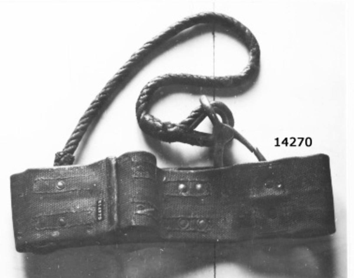 Livbälte. På bältets ena ände är fastsatta två söljor, på den andra  änden två remmar för fastsättning runt livet. Två rörliga ringar av järn i mässingsbeslag fastnitade på läder som är fastsytt på bältet. En 950 mm lång 3-slagen lina med splitsade öglor med kaus i båda ändar är med sin ena ände fast till den ena ringen på bältet, den andra änden på linan är försedd med karbinhake och är avsedd  att haka fast i den andra ringen, då linan är lagd runt masten.