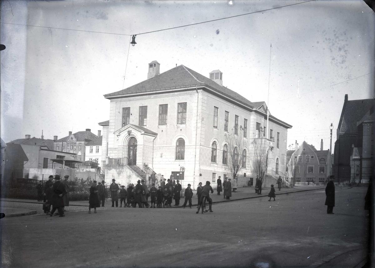 Haugesund Posthus i Torgbakken. Fotografert fra sørvest. Vår Frelsers kirke skimtes helt til h. Mange personer på fortauet og i gata.