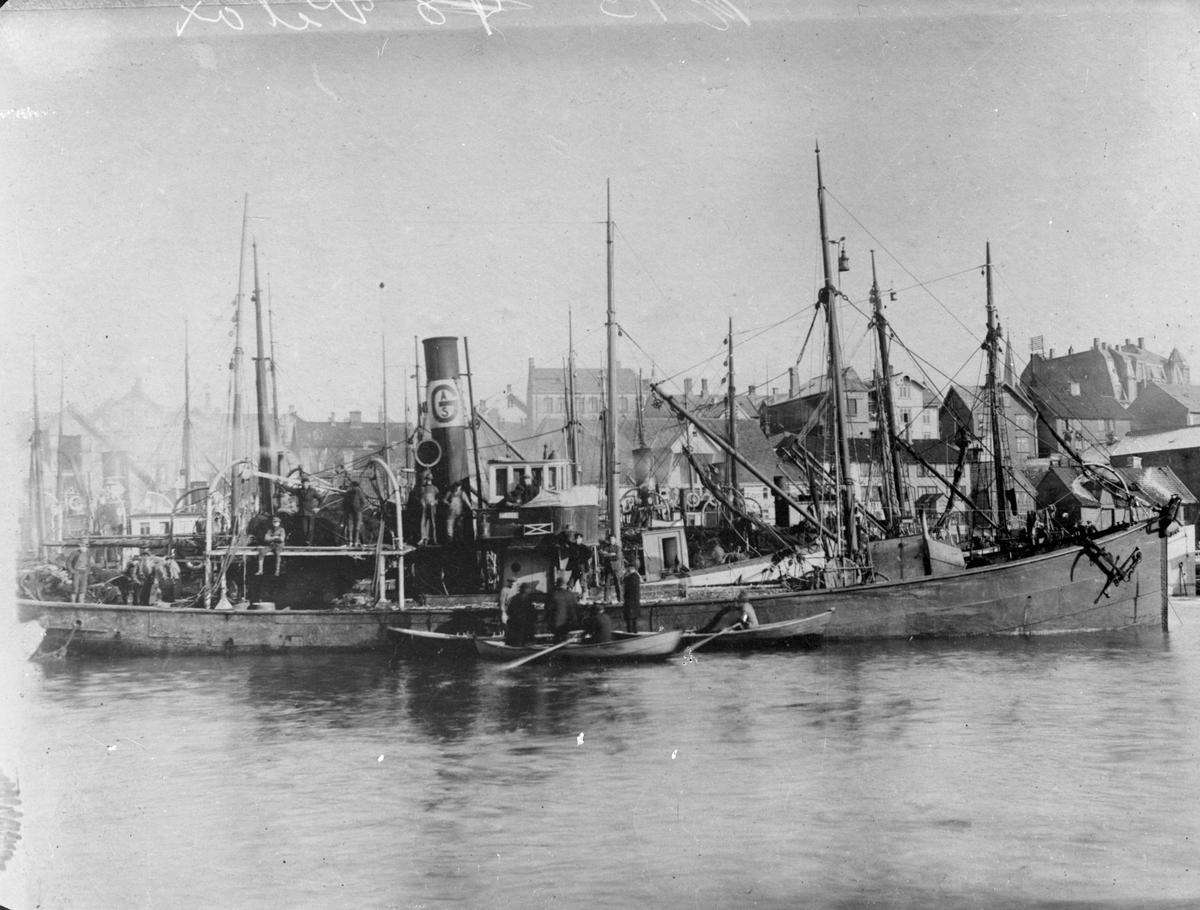 """Dampskipet """"Velox"""" ved havn i Smedasundet, Haugesund. Det er flere menn ombord og noen småbåter har rodd ut til båten. Handelstandens hus ligger bak til høyre. Grønhauggata går opp bak skipene. Skipet ligger utenfor flere andre dampskip."""