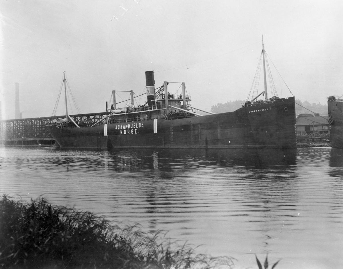 """Dampskipet D/S """"Johan Mjelde"""" ved havn på et industristed."""