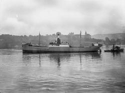 """Dampskipet D/S """"Johan Mjelde"""" ved en ukjent by."""