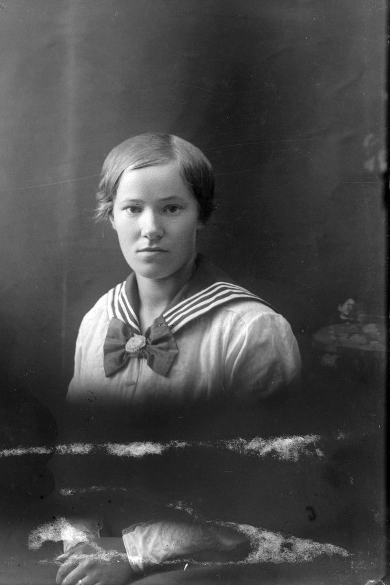 Studioportrett av en ung kvinne i halvfigur.