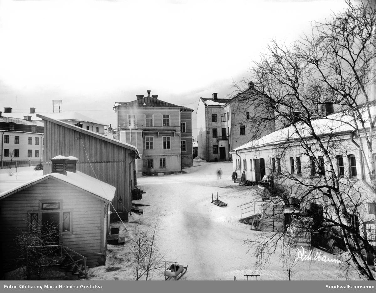 """Lindgrenska arbetsinrättningen. gården i kv Åmotet 4. I mitten arbetsinrättningens gavel, t h """"gamla"""" ålderdomshemmet och stallbyggnaden, bägge från 1890."""