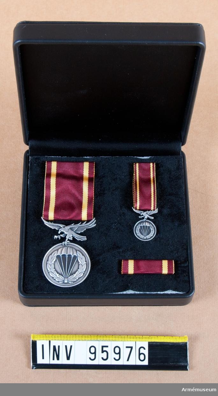 Medalj, miniatyr och släpspänne i ask.