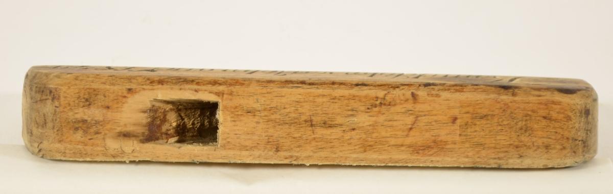 Rektangulær trekloss med avrundete topphjørner, og en hevet kant langs nederste langside. Skråstilt gjennomgående forkantet hull med en liten avrundet uthuling til å plassere blad og kile.   På den ene siden  er den nedre kanten lett avskjæret innover. Det er også innskjært et navn på denne siden. Det er også spor etter et innsvidd bumerke på begge langsider  Smal høvel til å høvle spor eller kant i listverk. Høvelen mangler blad.