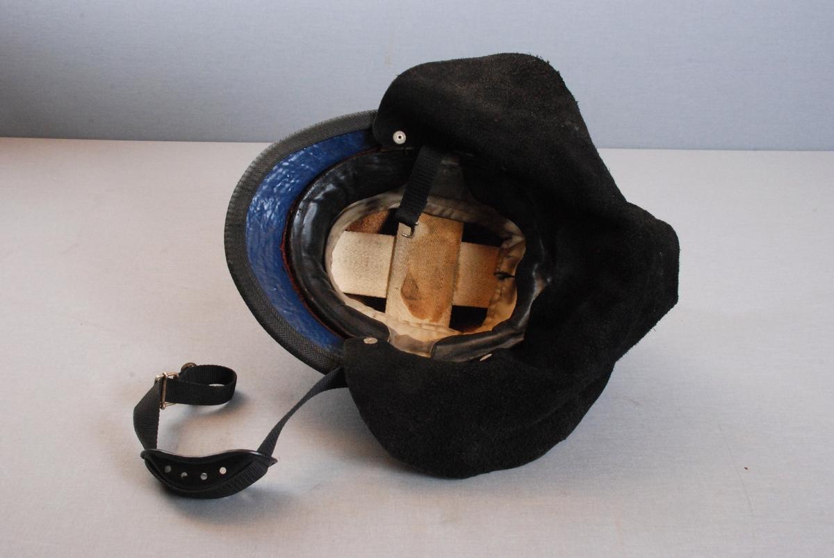 Brannhjelm i plast med støpt hanekam på toppen. Hjelmen har sammenhengende brem foran og bak, medplastkant rundt. Innerfor av tekstil besatt med skinn. Foret kan reguleres med snor. Hakereim i tekstil, med plast hakebeskytter. Nakkeskinn festet med trykknapper. Hjelmen har Bergen byvåpen emblem i front. metallkrans formet som ekeløv feste til hjelmens sider.