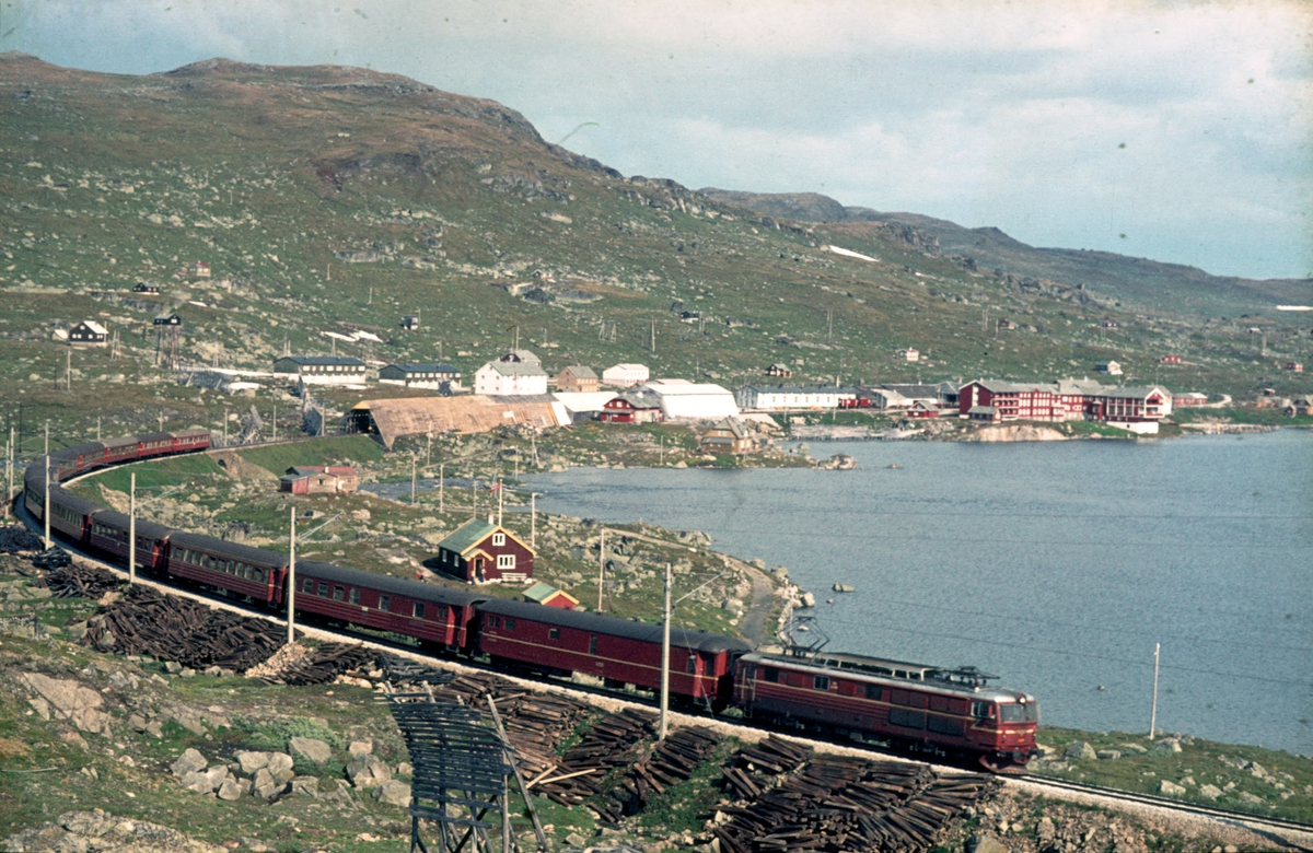 Langs Rallarvegen. Bergensbanen ved Finse stasjon. Daghurtigtog 601 Oslo Ø - Bergen på vei ut av stasjonen. Lokomotiv type El 14.