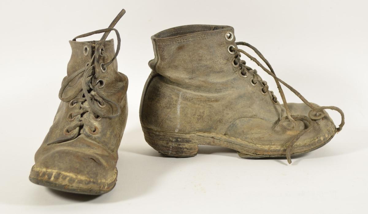 Barnesko med 7 hull for snøring. Begge skoene har blitt omsålet flere ganger, det kan sees på antallet sifter som er slått i sålene. Begge skoene har lærlisser.