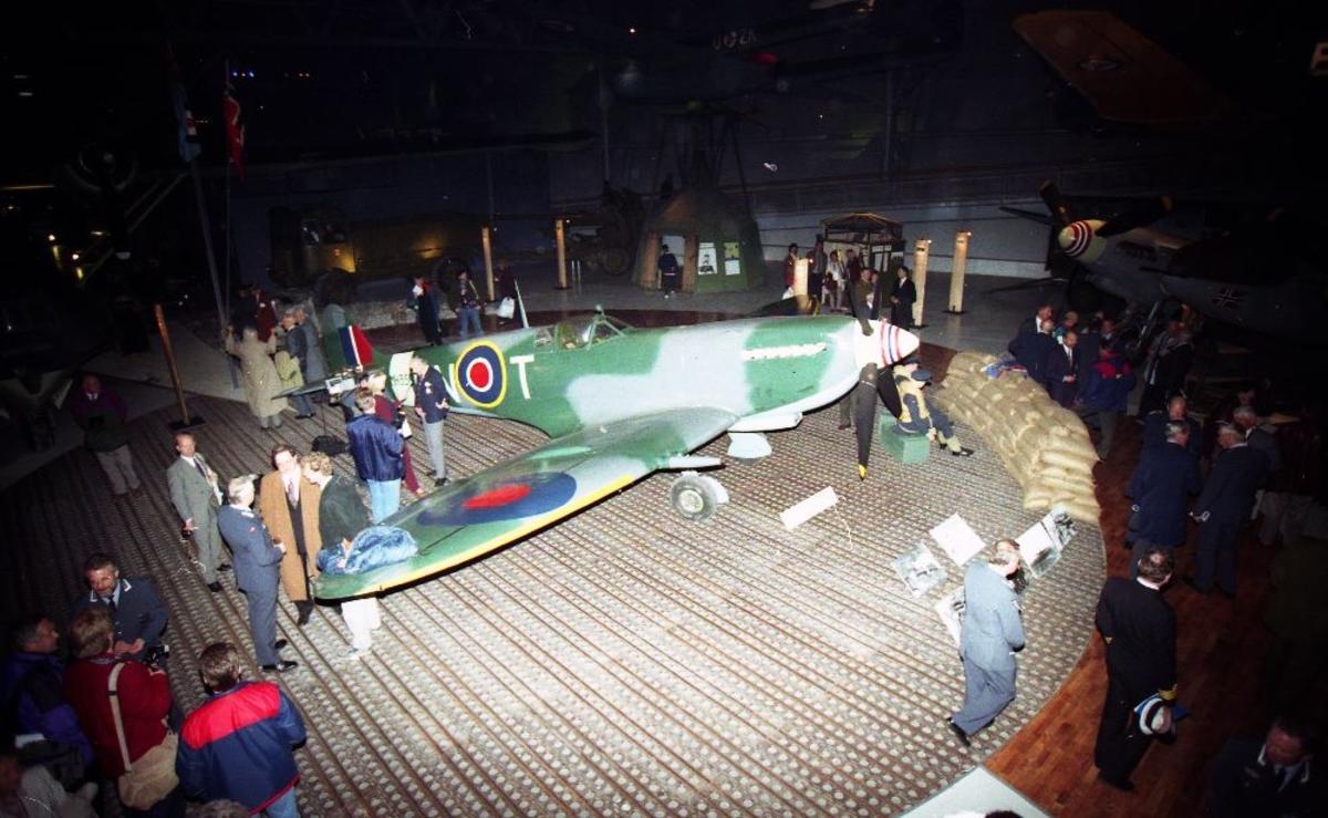 Flere personer samlet rundt  en Spitfire. Tatt innendørs.