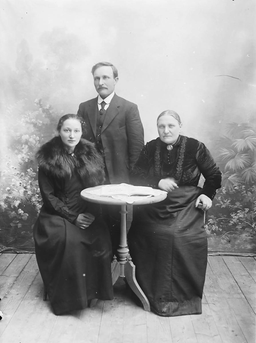 Gruppebilde. En mann og 2 kvinner ved et lite, rundt bord. Kvinnene sitter ved bordet. Mannen står bak dem.