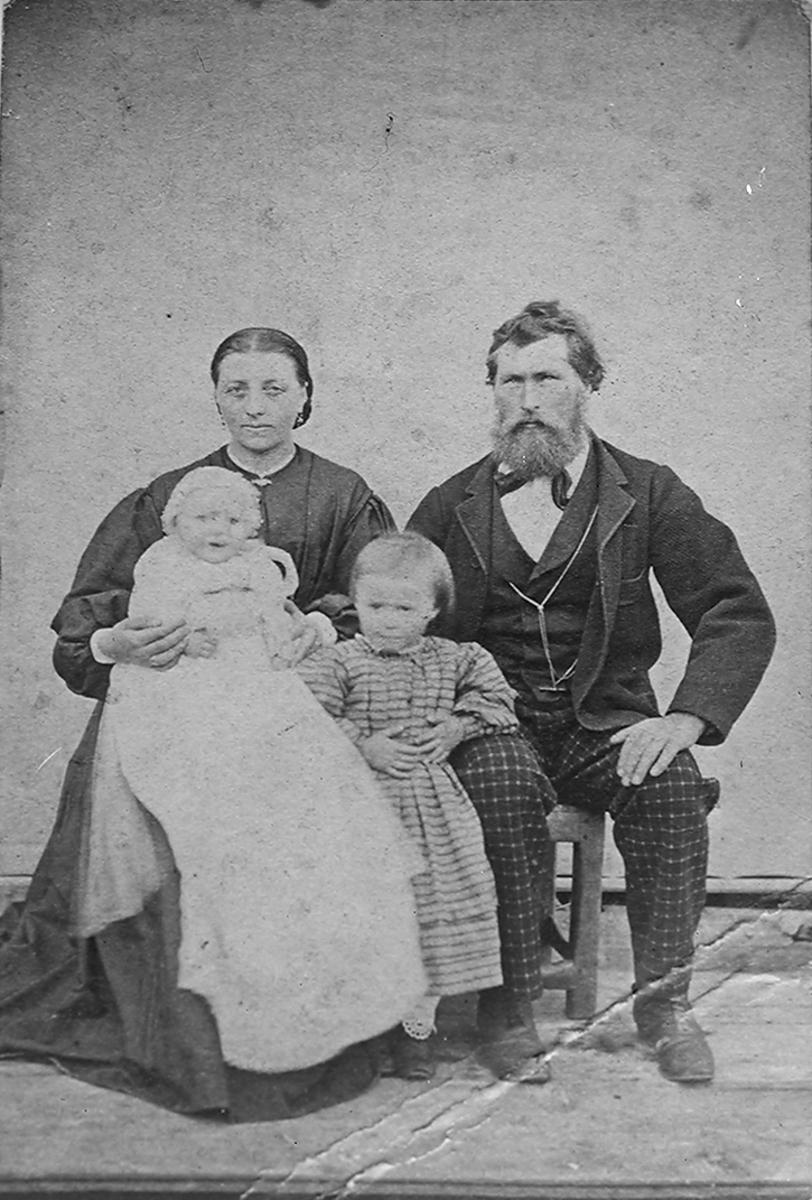 Familieportrett, mor, far og 2 barn. Mor og far sitter, den ene ungen; datter står mellom moren og faren. Et lite barn, dåpsbarn (?) sitter på fanget til moren.