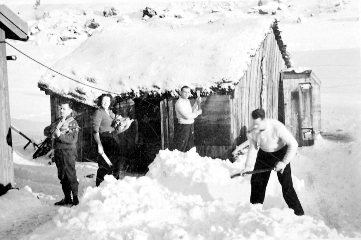 Gruppebilde. 4 pertsoner, kvinner og menn ved noen bygninger. Snø på bakken