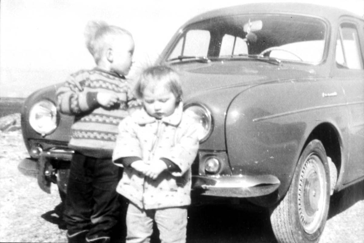 Gruppebilde. 2 personer, barn. Utendørs ved et kjøretøy - personbil,Renault Dauphine 1956-67.