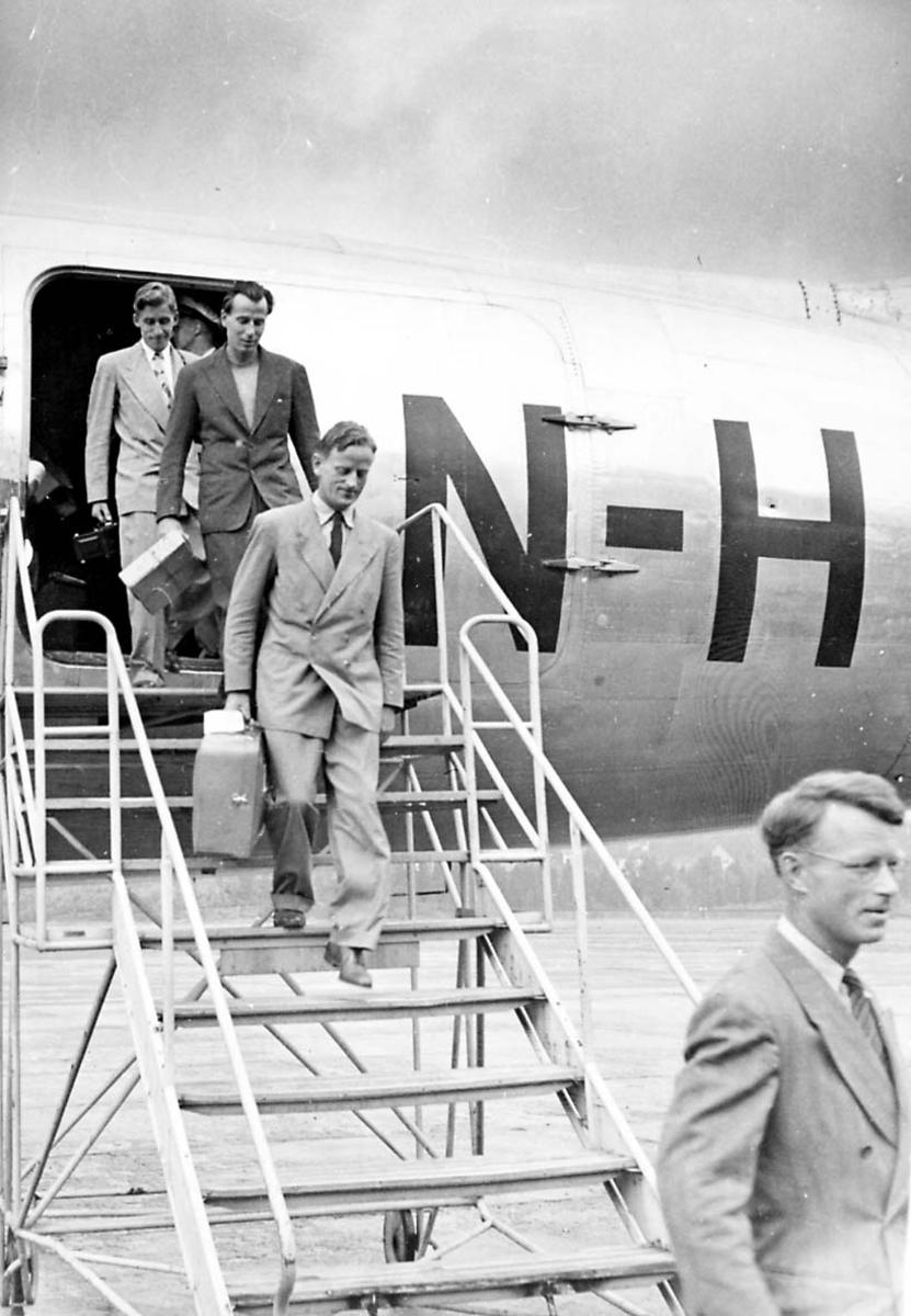 Lufthavn. 1 fly på bakken, Douglas DC-4 C-54 Skymaster fra Braathens SAFE. Noen personer på vei ned landgangen.