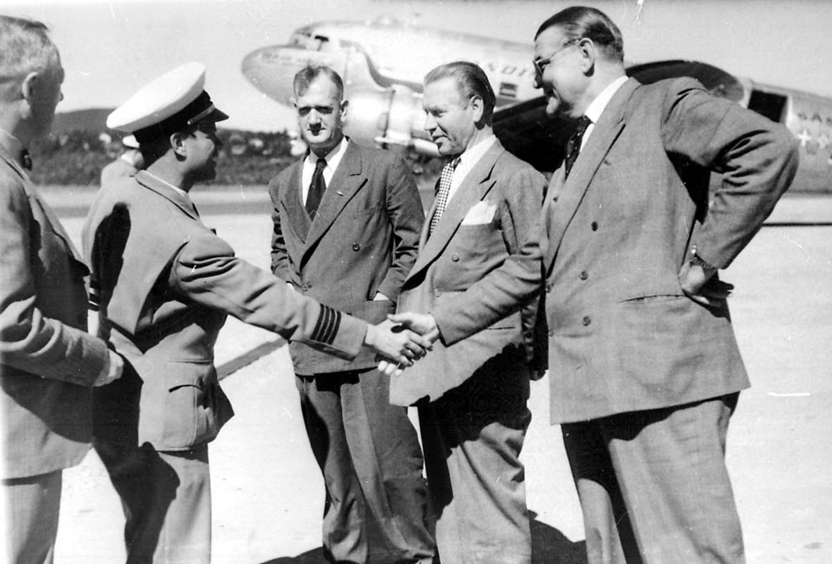 Lufthavn. Portrett 5 personer på rullebanen. 1 fly i bakgrunnen DC-4 C-54 Skymaster fra Braathens SAFE.