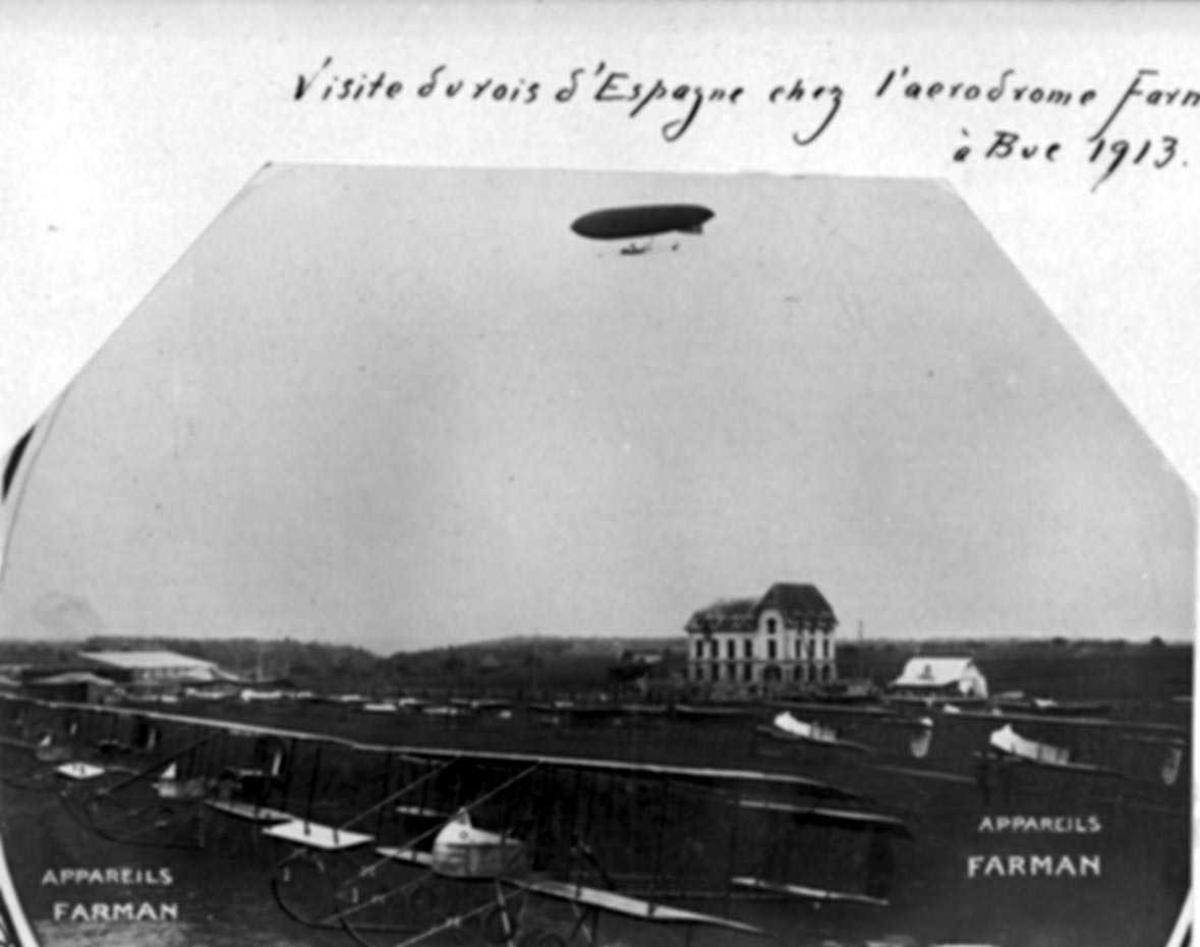 Flere fly oppstilt på bakken, Farman, MF.7 Longhorn. Mange personer ved flyene. Større bygning bak. Ett luftskip i lufta over området. ..