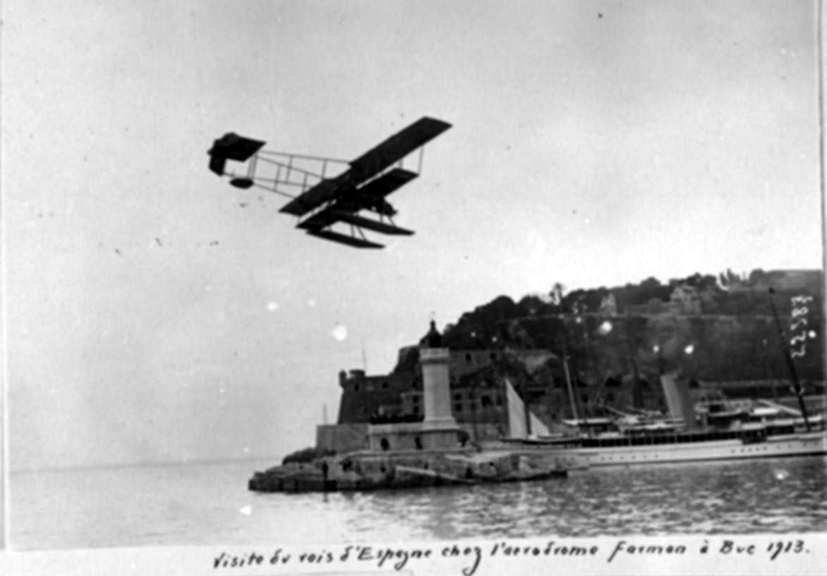 Luftfoto. Ett fly i lufta, Farman. Fyrtårn og bebyggelse i bakgrunnen.