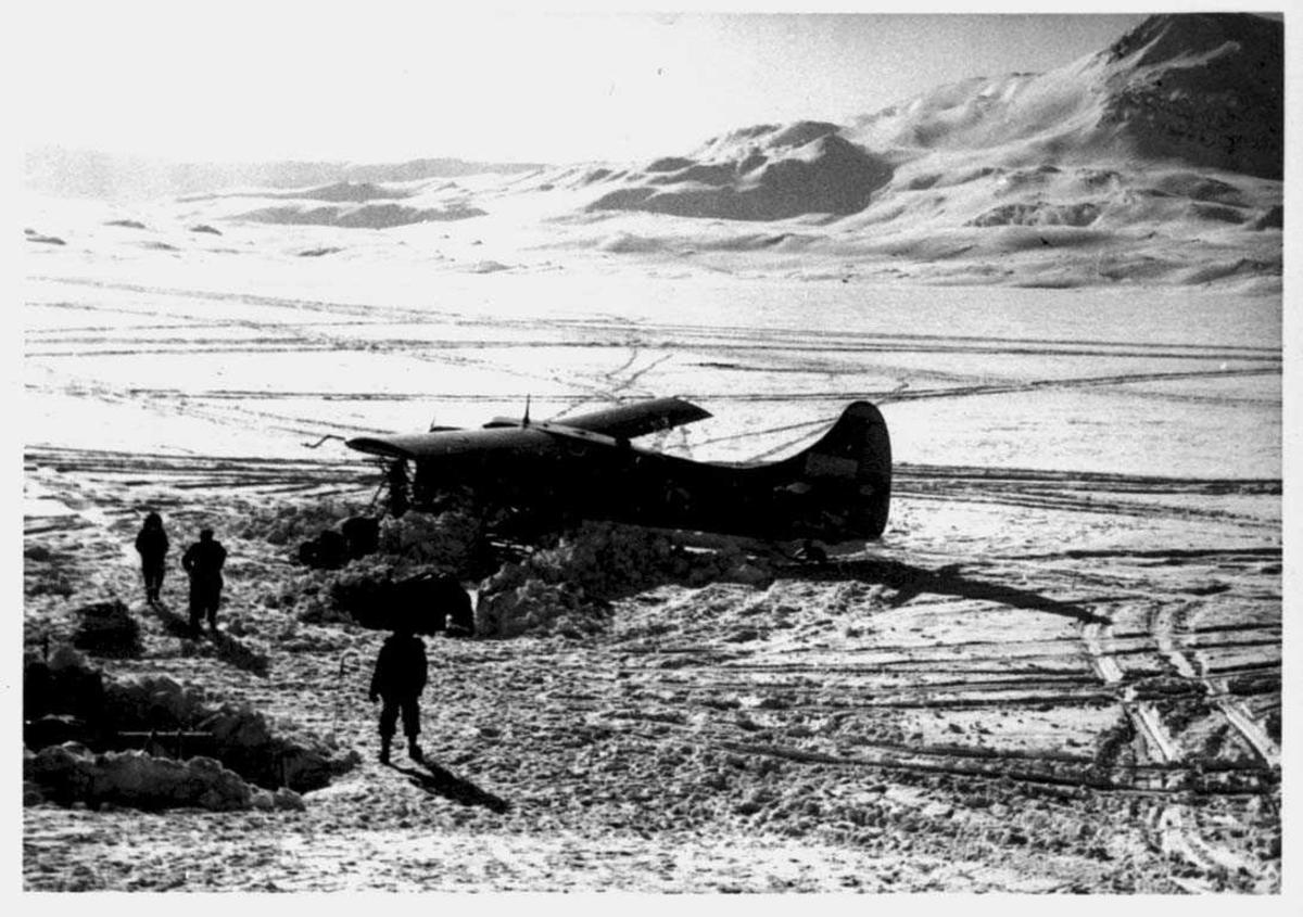 Snødekt landskap. Ett fly på bakken, Otter. Tre personer og noe utstyr ved flyet.