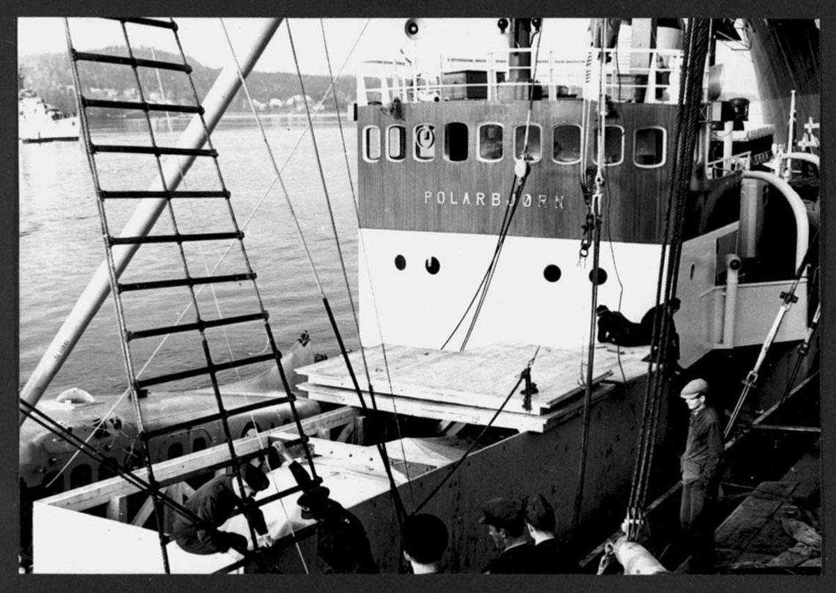 """En flykasse ombord i  polarskuta """"Polarbjørn"""". Noen personer ved kassen"""