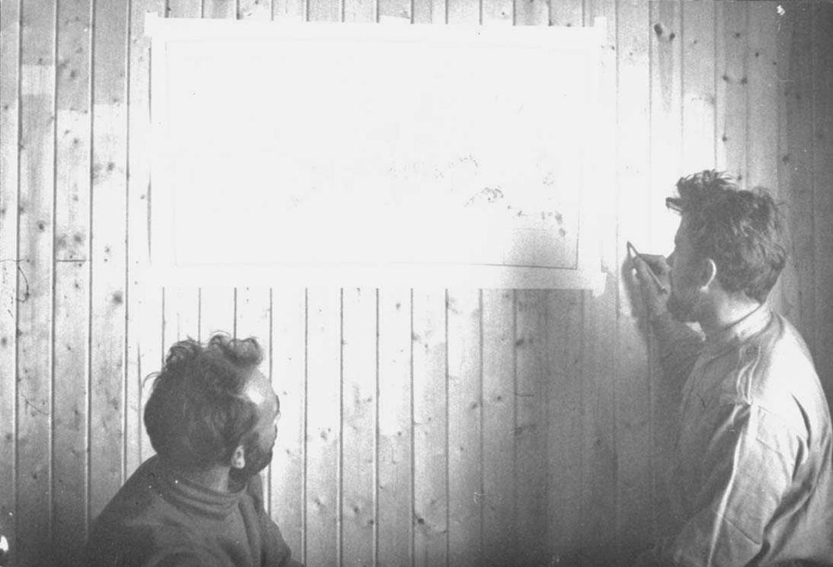 To personer innendørs, menn, studerer et kart.