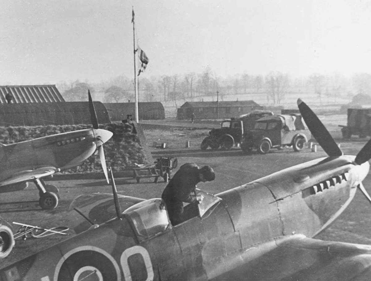 Jagerfly og militære kjøretøy på en alliert flybase.