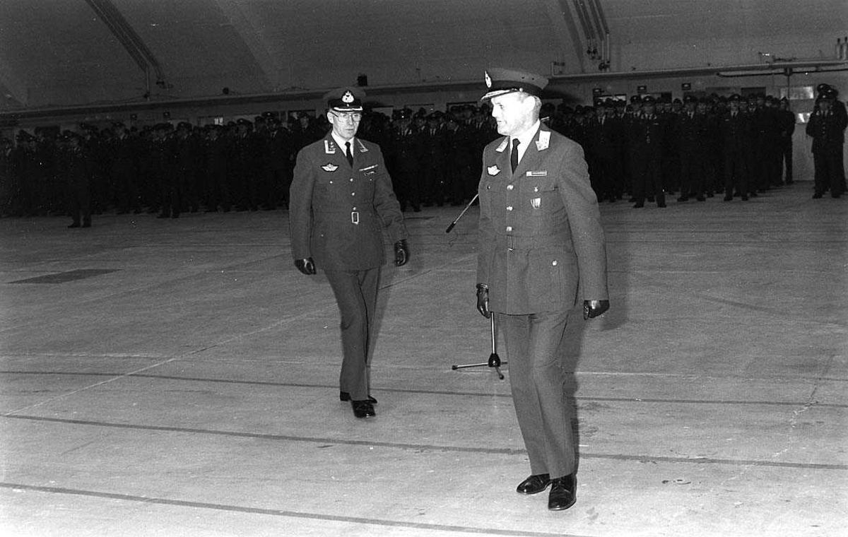 2 personer foran oppstilt personell i en hangar.