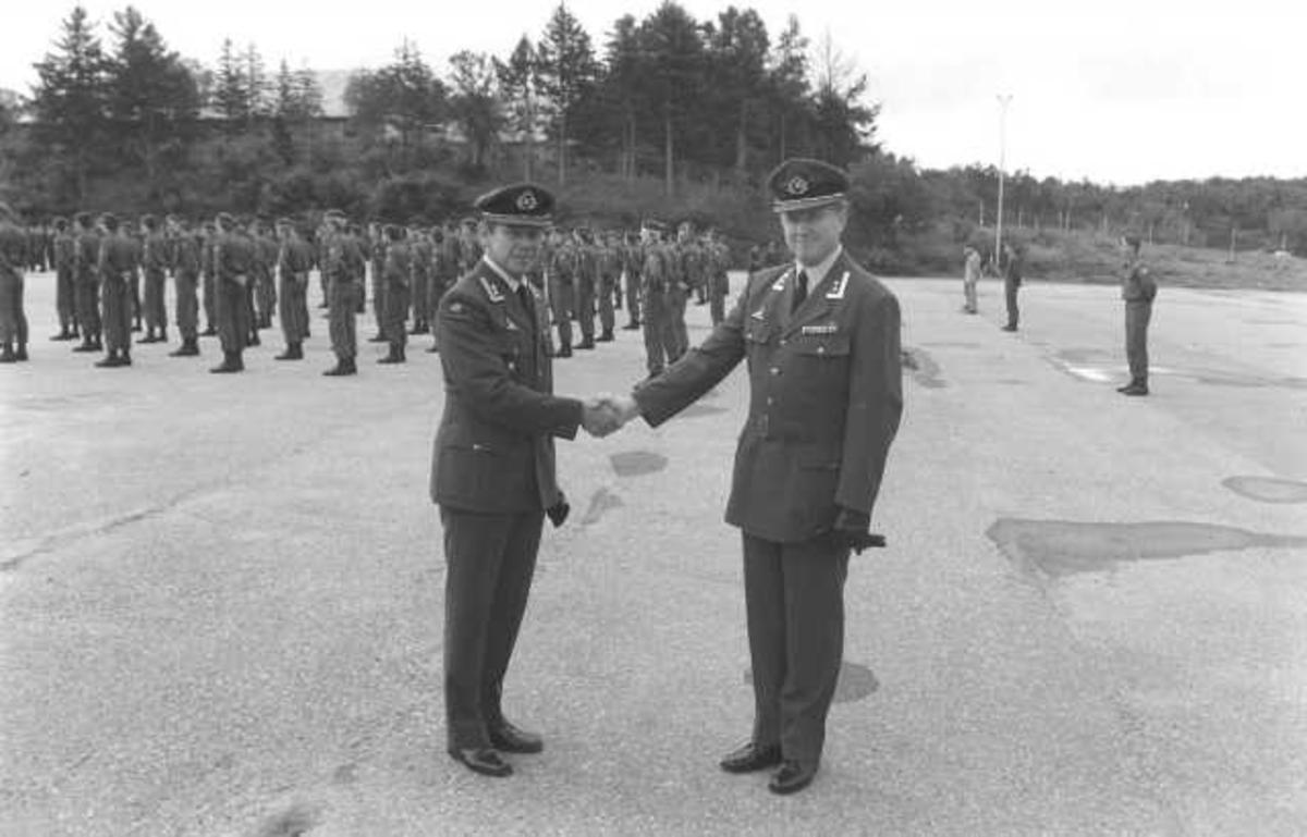 2 personer hilser på hverandre. Oppstilling av militært personell i bakgrunnen.