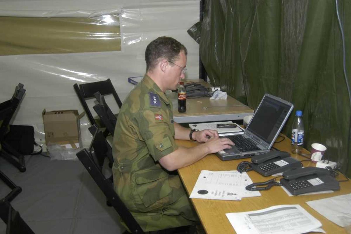 En person ved en PC (laptop). Tatt inne i et telt