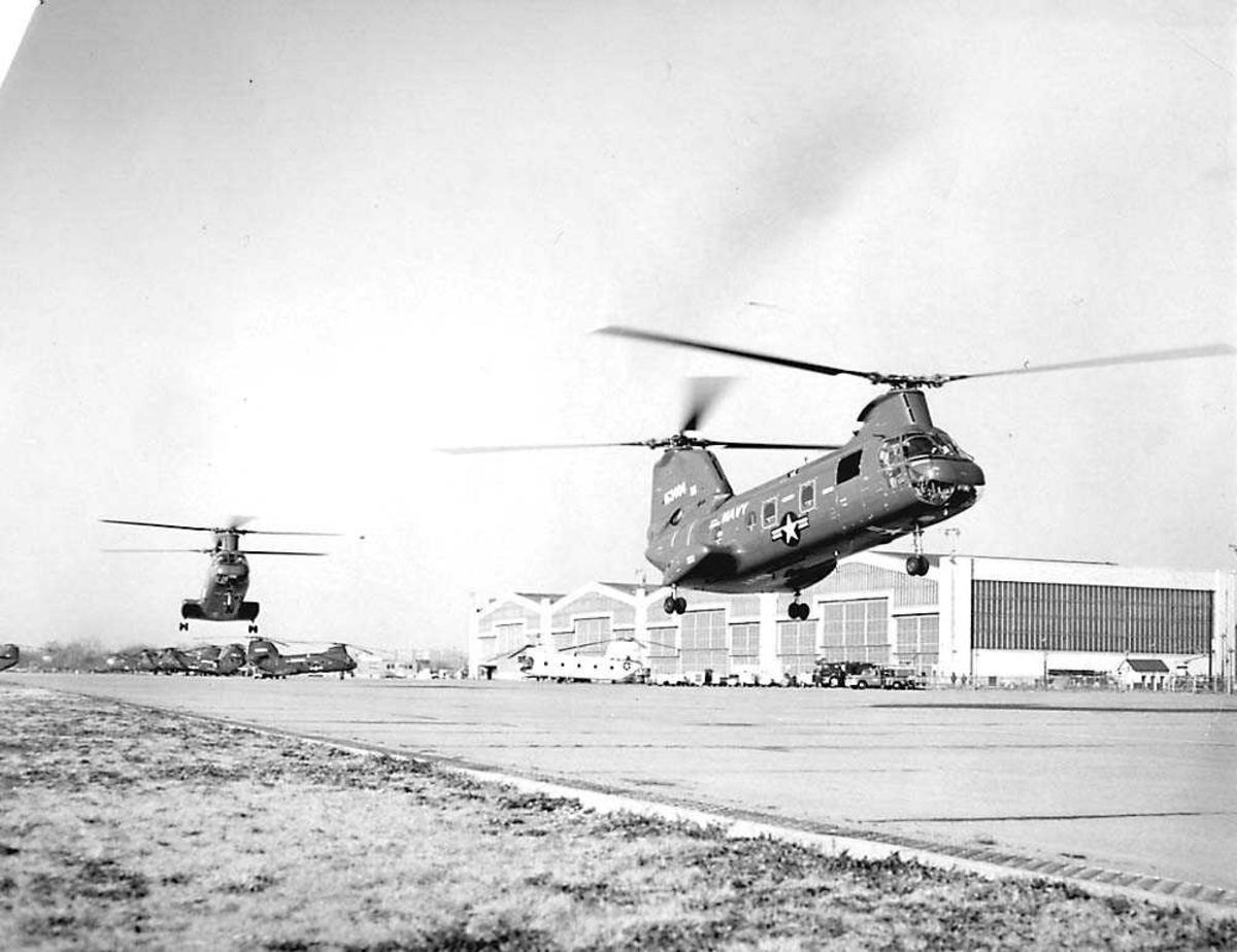 2 helikoptre i luften. Boeing Sea Knight UH-46D. Hangar og flere helikoptere i bakgrunnen.