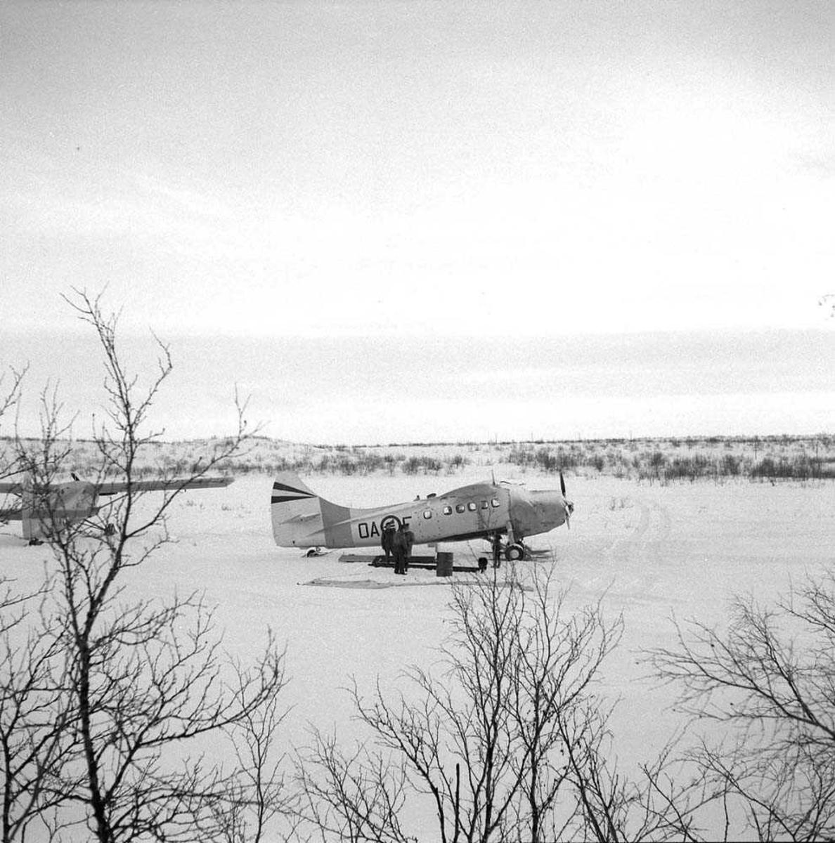 2 fly av typen DHC-3, Otter. Flyet midt i bildet har kjennetegn OA-F. Dette flyet skulle ta av fra Kautokeino flystripe. På grunn av mye is/rim på skiene fikk ikke flyet nok fart og kom borti et eller annet med vingen, som ble ødelagt.