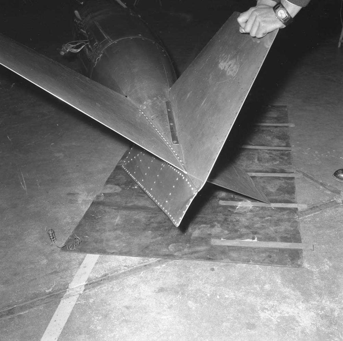 Arbeidsuhell på F-104 Starfighter i Hangar A på Bodø flystasjon. Dropptanken har falt av fra vingefestet ved at utløsermekanismen ble utløst ved en feil.