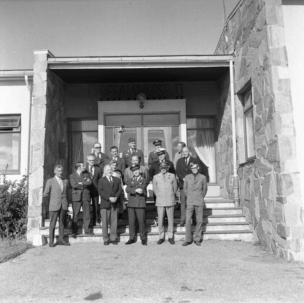 Gruppefoto av Forsvarskommiteens besøk på Bodø flystasjon, her fotografert foran Messe II på stasjonen. Oberstløytnant Olav F. Aamoth sees i første rekke som nr. 3 fra høyre. Oberst H. Wergeland sees helt bakerst i midten.