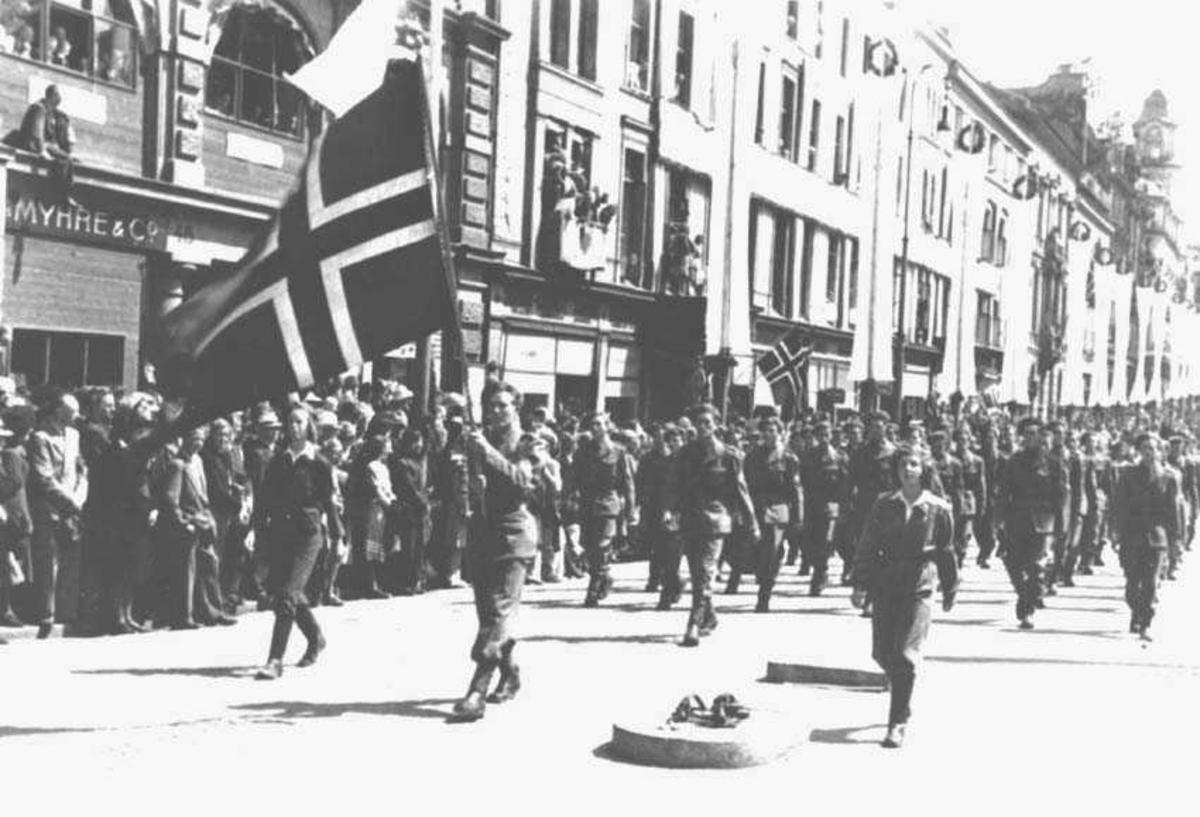 Militærtropp som masjerer i gaten. Den første bærer et norsk flagg. Folkemengde ved siden av. Bygninger i bakgrunnen.