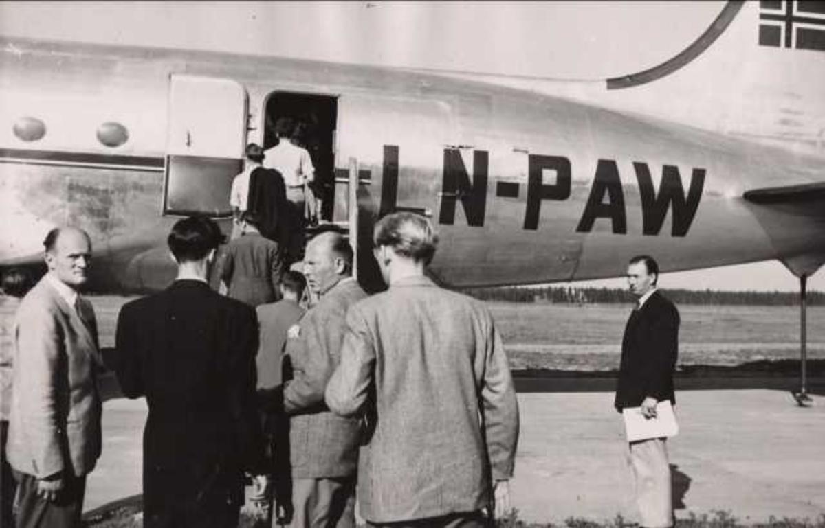 Ett fly på bakken. Douglas C-54A-15-DC Skymaster. LN-PAW. Flere personer ved flyet.