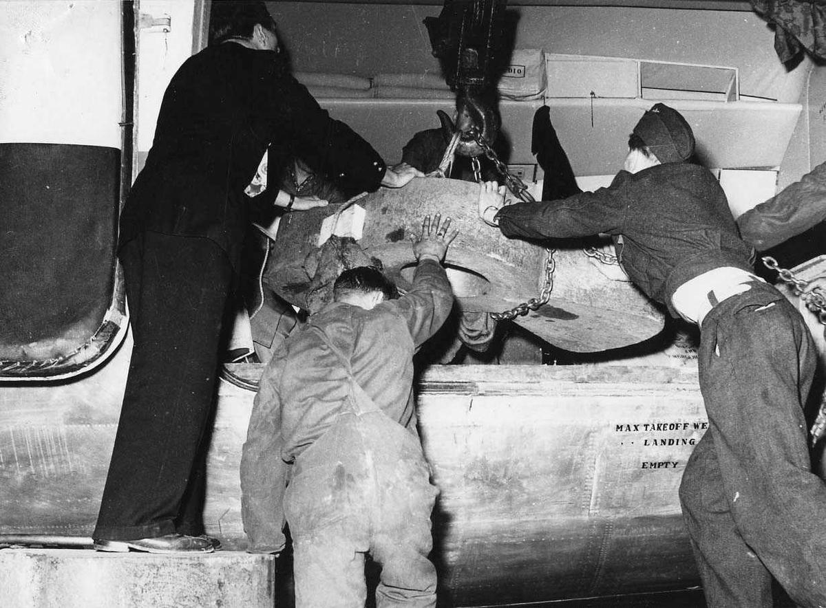 Ett fly på bakken. Douglas DC-4. Tre personer ved flyet. Lasting av gjenstand.