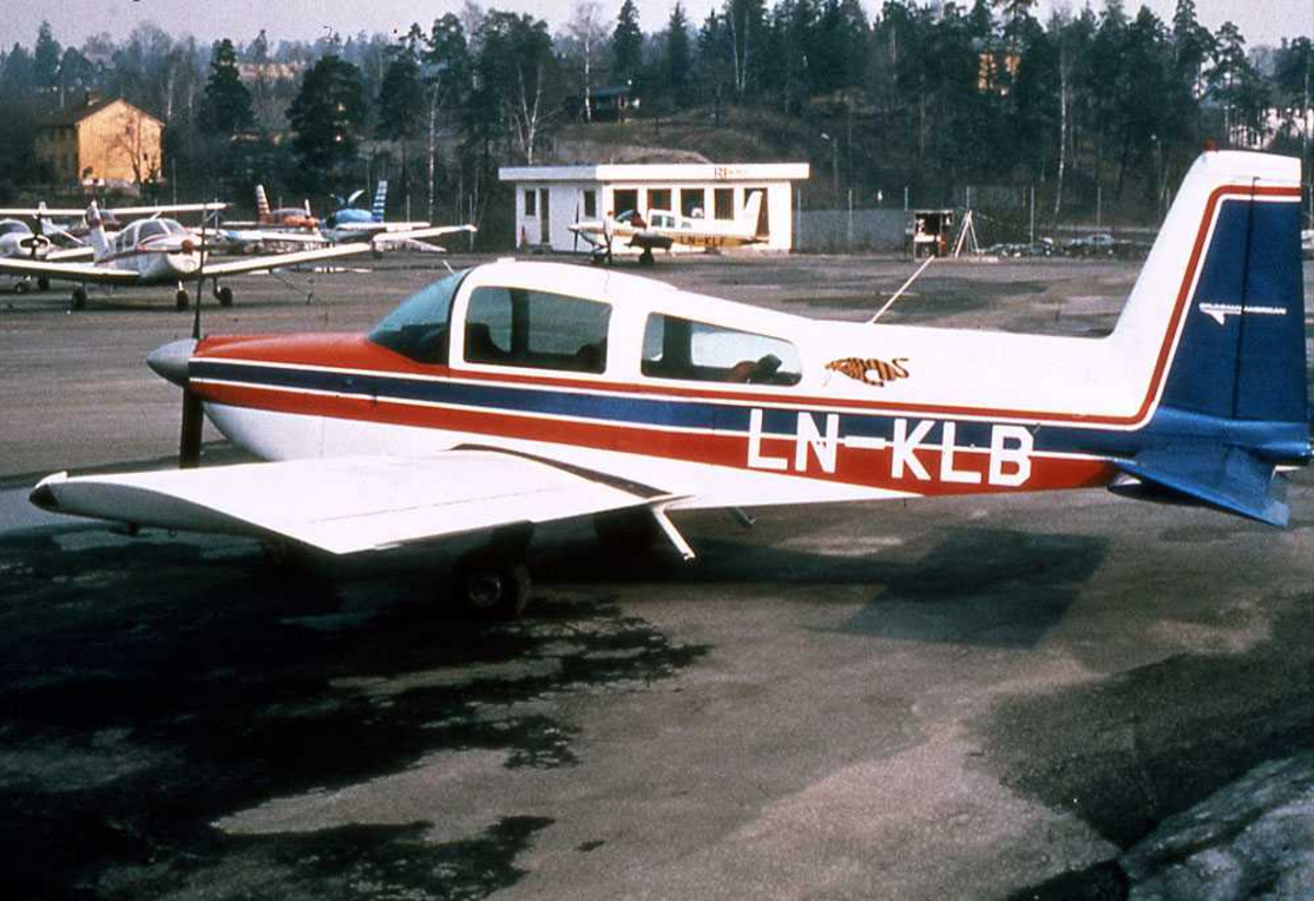 Ett fly på bakken. LN-KLB, Grumman American AA-5B Tiger. Flere småfly i bakgrunn.
