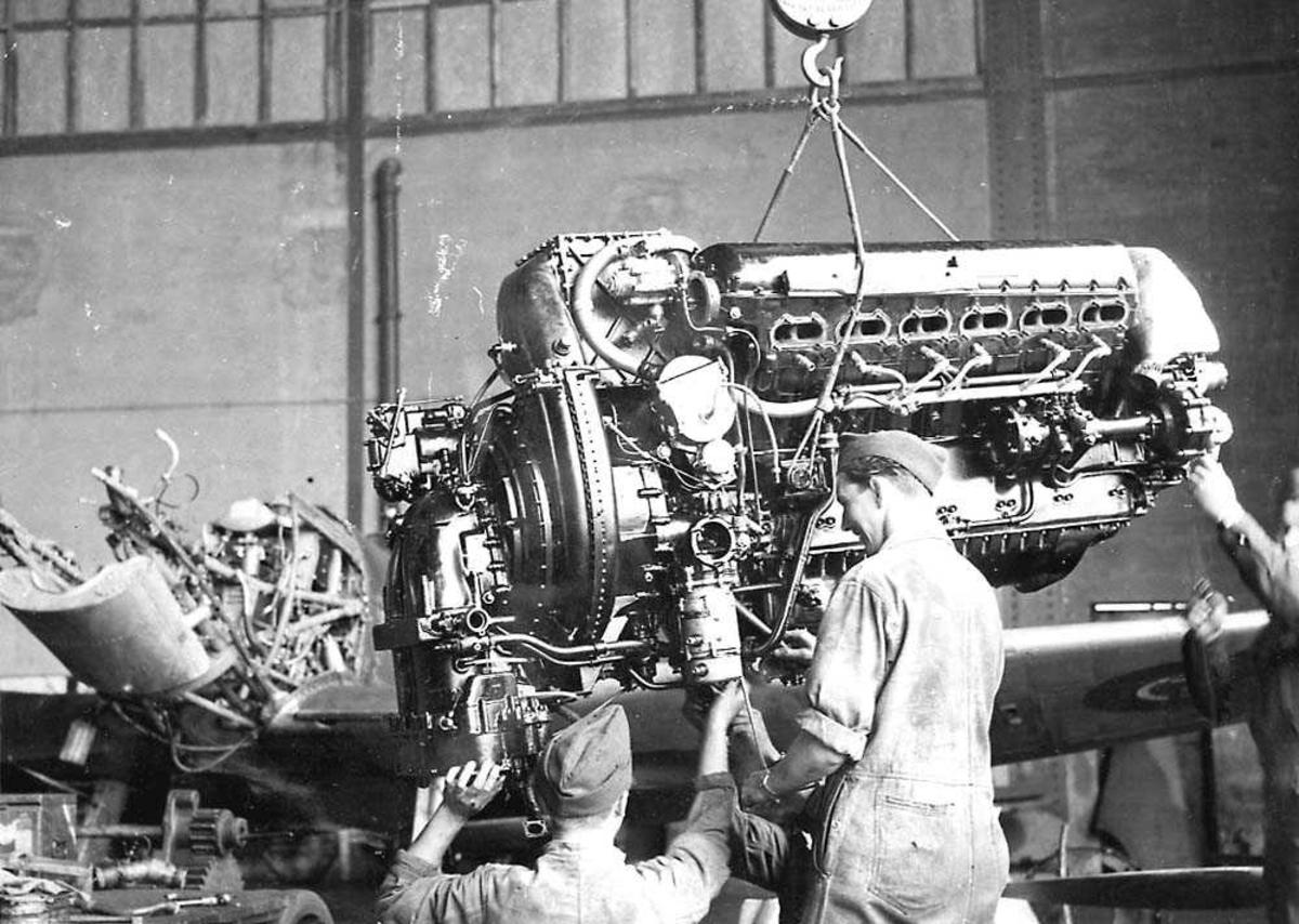 To personer som arbeider med en flymotor innendørs.