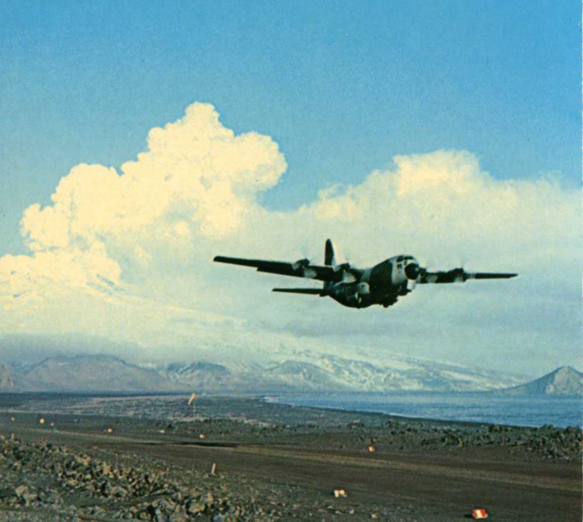 Postkort. Ett fly i luften like etter take-off, Hercules. Landingsstripe under flyet. Fjell i bakgrunnen.