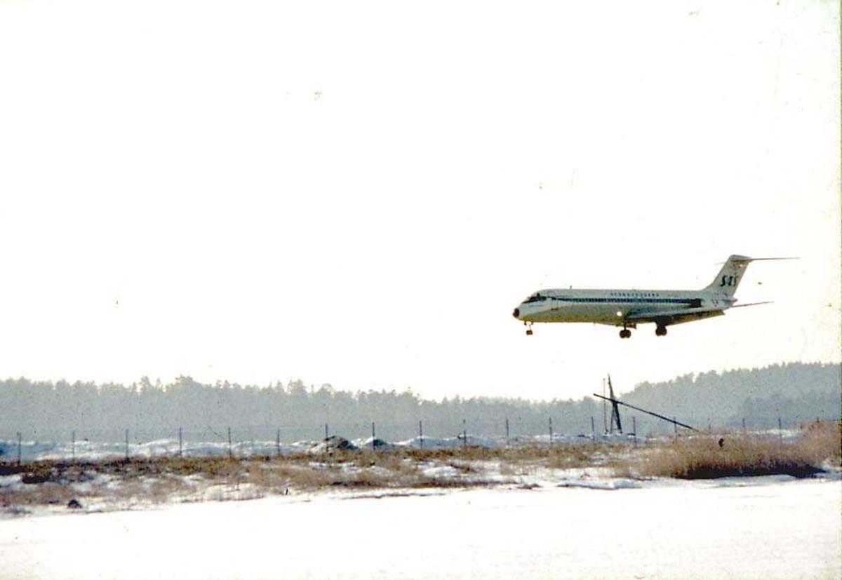 Luftfoto. Ett fly like over bakken før landing, McDonnell Douglas DC-9 - 21/ -33/ -41 fra SAS. Snø på bakken.