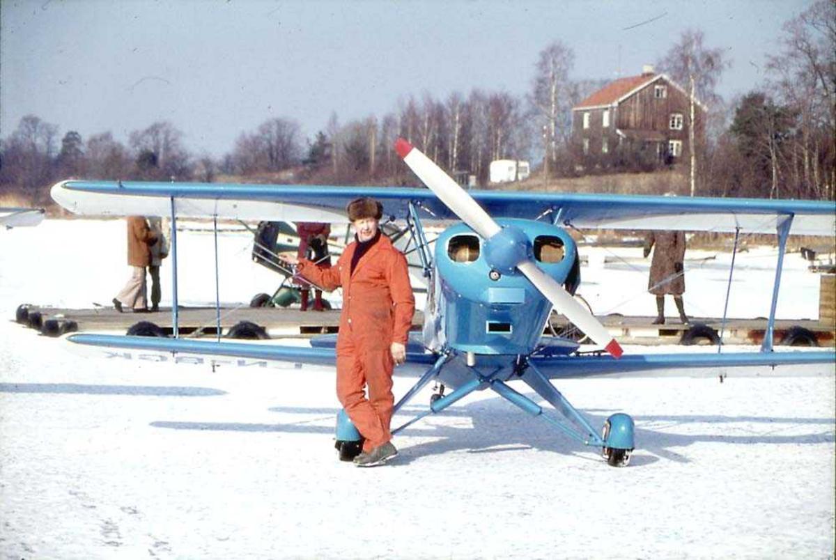 Ett fly ute på et isdekt vann, EAA Acro Sport, LN-BGK. En person, mann, står foran flyet. Flere personer på ei trekai og en bygning i bakgrunnen.