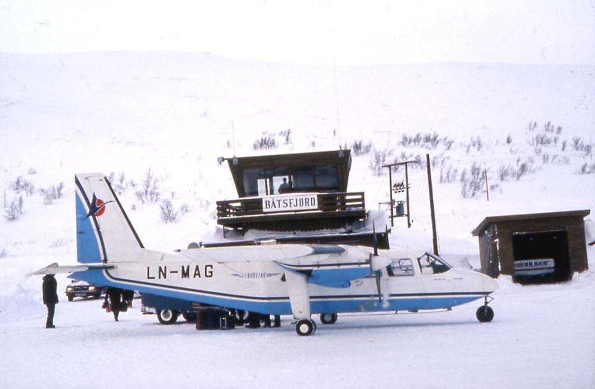 Lufthavn. Ett fly på bakken, Britten-Norman BN-2A Islander, LN-MAG fra Norving. Flyplassbygninger og personer i bakgrunnen. Snø på bakken.