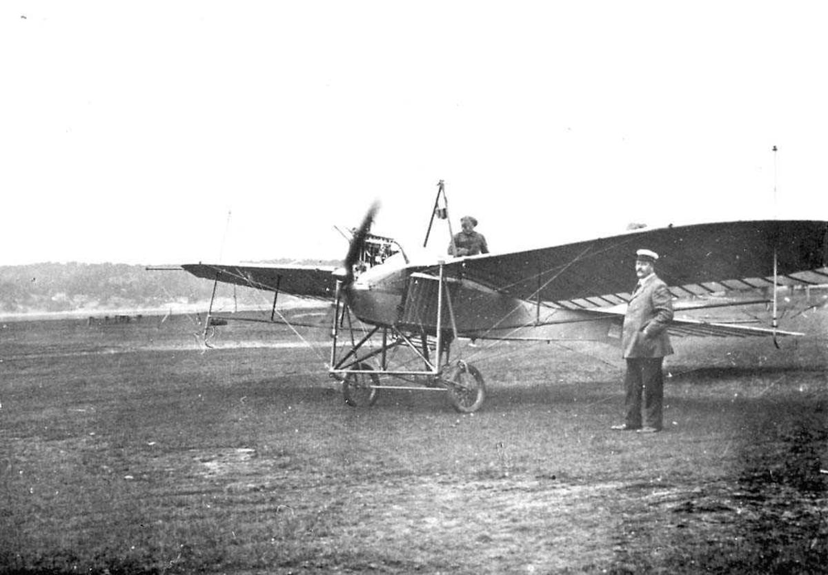 """Ett fly på en åpen plass, Rumpler Taube """"Start"""". En person står ved flyet, en person i cockpiten."""